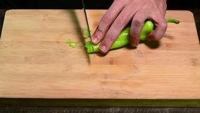 Cortando a pimenta verde com a faca na placa de madeira video estoque