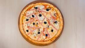 Cortando a pizza com presunto e queijo na placa de madeira na tabela Opini?o do Close-up video estoque
