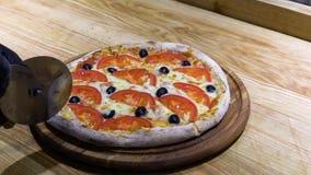 Cortando a pizza cozida fresca com faca e adição da roda do óleo nele no movimento lento video estoque
