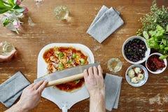 Cortando a pizza orgânica com faca da pizza Imagens de Stock