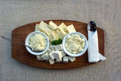 Cortando queijos diferentes em uma bandeja de madeira fotos de stock