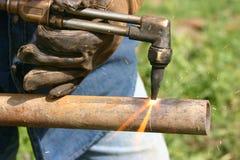 Cortando a tubulação de aço com tocha Fotos de Stock Royalty Free
