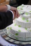 Cortando um bolo de casamento imagem de stock