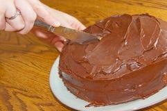 Cortando um bolo de chocolate imagem de stock royalty free