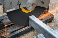 Cortando um metal e um aço quadrados com mitra composta viu fotos de stock