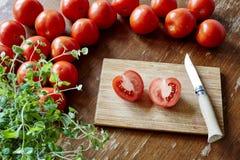Cortando um tomatoe na cena da cozinha foto de stock royalty free