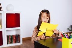 Cortando uma casa em um papel vermelho Foto de Stock