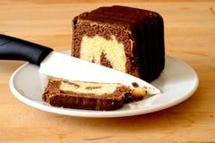 Cortando uma fatia de bolo marmoreado do chocolate delicioso, com um whit Foto de Stock
