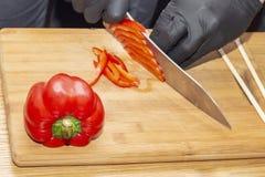 Cortar al cocinero de la paprika cocinar la comida sana sana de la dieta tabla de cortar de madera en la tabla de madera, manos d fotos de archivo