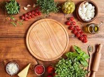 Cortar al tablero de madera con los ingridients tradicionales de la preparación de la pizza: mozzarella, salsa de tomates, albaha Imagen de archivo