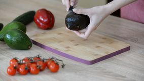 Cortar el aguacate fresco en una tabla de cortar de madera metrajes