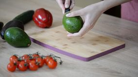 Cortar el aguacate fresco en una tabla de cortar de madera almacen de metraje de vídeo