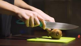 Cortar el kiwi en medio ‹cortado del †del ‹del †en un tablero verde claro metrajes