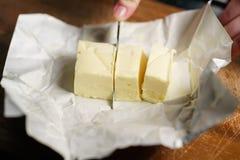 Cortar el ladrillo de la mantequilla con el cuchillo Fotografía de archivo
