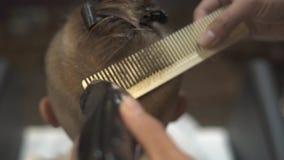 Cortar el pelo de los niños con la maquinilla de afeitar eléctrica y el peine en barbería Corte de pelo ascendente cercano del mu almacen de metraje de vídeo