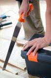 Cortar el tablón de madera con la sierra de la mano Fotos de archivo