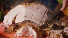 Cortar la carne asada para la tabla del día de fiesta Cortes del cocinero que cuecen la carne al vapor asada a la parrilla almacen de metraje de vídeo
