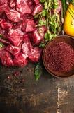 Cortar la carne cruda con las especias y las hierbas frescas, ingredientes para el cocido húngaro que cocina en el fondo de mader Imagen de archivo