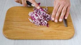 Cortar la cebolla en tabla de cortar de madera almacen de metraje de vídeo