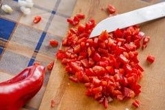 Cortar la paprika y cebollas rojas dulces en tabla de cortar de madera imagen de archivo libre de regalías