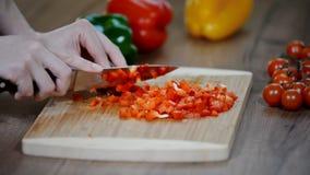 Cortar la pimienta roja fresca Pimienta fresca en un tablero de madera Verduras del corte del cocinero con un cuchillo almacen de metraje de vídeo