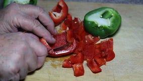 Cortar la pimienta roja y el cortar en pedazos almacen de video