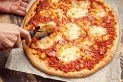 Cortar la pizza Fotografía de archivo libre de regalías