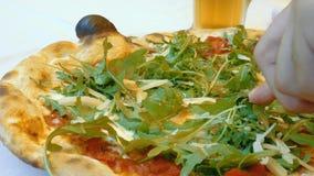 Cortar la pizza italiana remató con el queso parmesano y el arugula delicioso almacen de metraje de vídeo