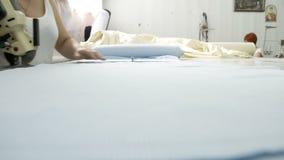 Cortar la tela, trabajo de costura Sala de despiece, manos de la mujer que cortan el cuchillo azul de la adaptación del paño metrajes