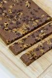 Cortar los brownie hechos en casa en fondo de madera Imagenes de archivo