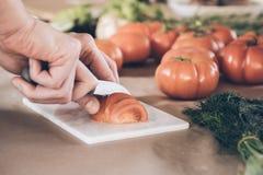 Cortar los tomates frescos en tabla de cortar fotos de archivo libres de regalías