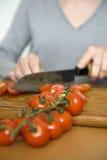 Cortar los tomates frescos para la cena Fotos de archivo libres de regalías