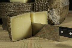 Cortar un queso de Manchego Curado en pedazos con el cuchillo doble-dirigido Fotos de archivo libres de regalías