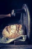 Cortar una barra de pan fresca en la cortadora Fotografía de archivo libre de regalías