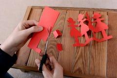 Cortar una cadena de muñecas de papel rojas con las tijeras foto de archivo