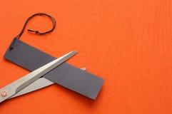 Cortar una etiqueta negra en fondo anaranjado imágenes de archivo libres de regalías
