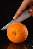 Cortar una naranja fresca con el cuchillo Imagen de archivo