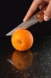 Cortar una naranja fresca con el cuchillo Imágenes de archivo libres de regalías