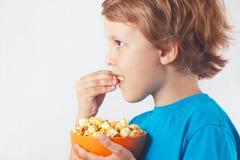 Corte al niño que come las palomitas Foto de archivo libre de regalías