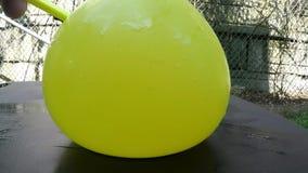 Corte amarillo del globo con una cámara lenta del cuchillo afilado almacen de video