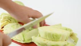 Corte a couve fresca com uma faca em uma placa de corte vídeos de arquivo