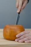Corte da pessoa com faca uma fatia de roda do queijo Imagem de Stock