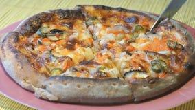 Corte da pizza em fatias usando uma faca de aço vídeos de arquivo