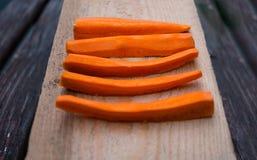 corte das cenouras nas tiras ajustadas no fim de madeira da placa acima das cenouras crus fotografia de stock royalty free