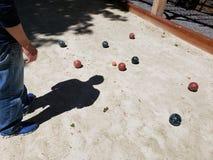 Corte de Bocce con la sombra de un hombre que estudia el juego Fotografía de archivo libre de regalías