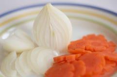 Corte de cebollas y de la zanahoria en una placa 2 Foto de archivo