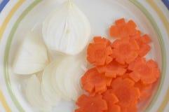 Corte de cebollas y de la zanahoria en una placa 4 Fotos de archivo libres de regalías