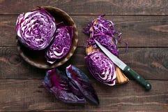 Corte de la col roja en pedazos con un cuchillo en un fondo de madera oscuro Ingrediente para cocinar los platos vegetales Imágenes de archivo libres de regalías