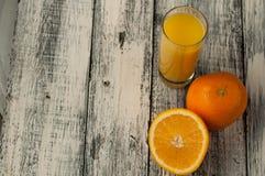 Corte de la fruta y zumo de naranja anaranjados en fondo de madera de la tabla, Imágenes de archivo libres de regalías