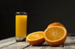 Corte de la fruta y zumo de naranja anaranjados en fondo de madera de la tabla, Fotografía de archivo